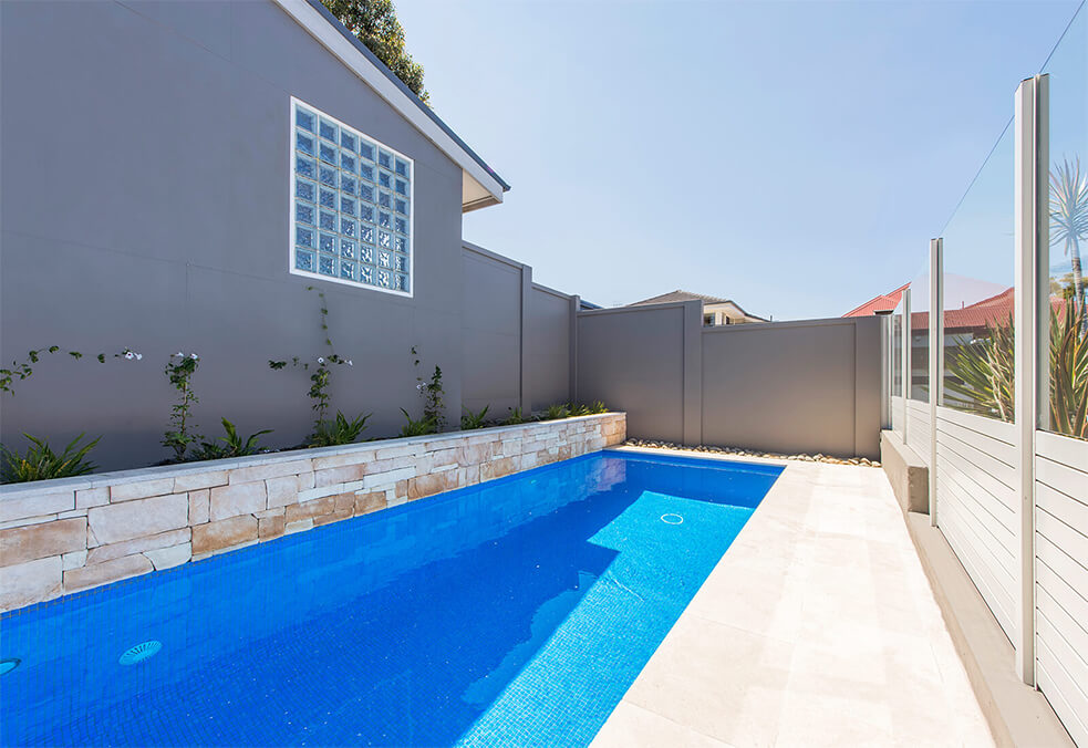 Sloping boundary pool wall for lap pool