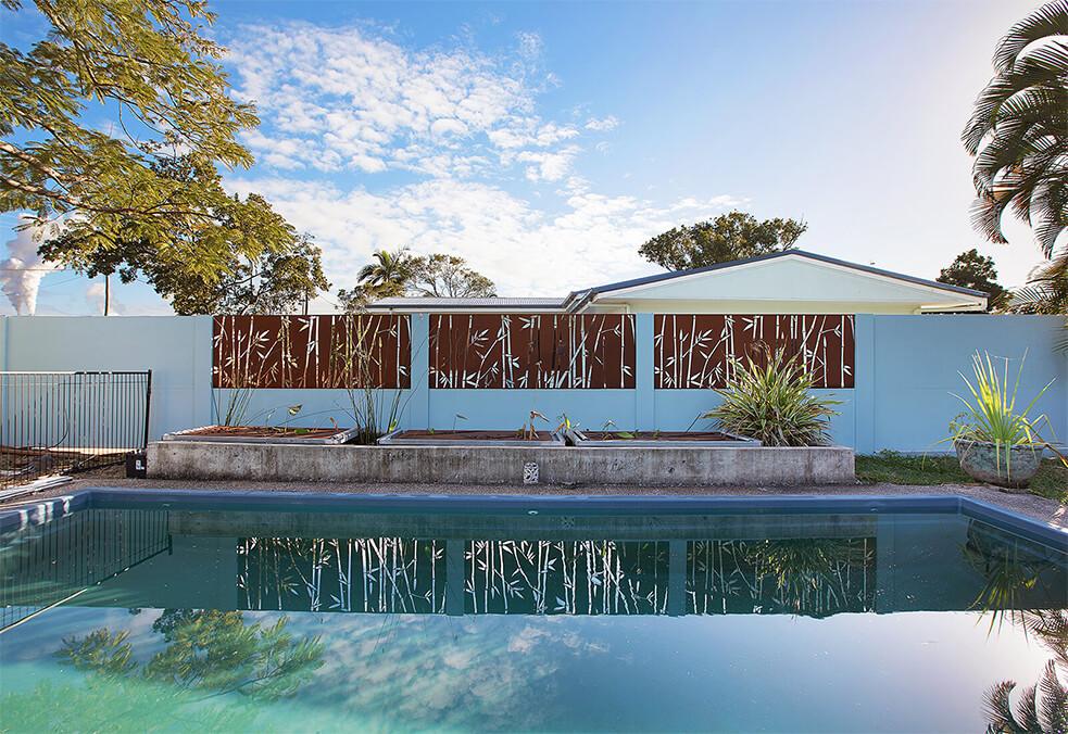 Pool boundary wall with custom bamboo lasercut coreten infills