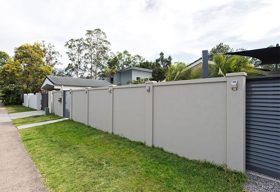Front privacy wall with sliding driveway gate and integrated lighting
